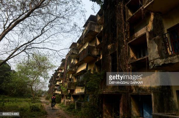 In this photograph taken on February 13 a cyclist rides past a building of the former employee housing complex at the Hindustan Motors campus in...