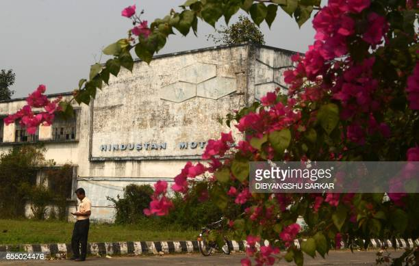 In this photograph taken on February 13 a former Hindustan Motors employee walks past a sign at the entrance to the building which used to house the...