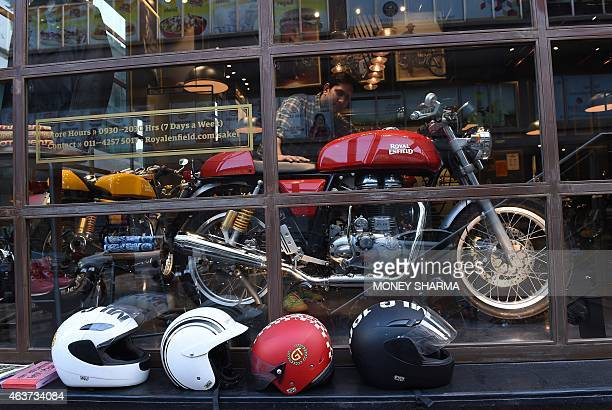 In this photograph taken on February 13 an Indian customer looks at a Royal Enfield Continental GT motorcycle on display at a showroom in New Delhi...