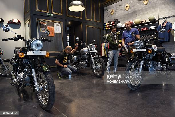 In this photograph taken on February 13 Indian customers and salesmen look at Royal Enfield motorcycles at a showroom in New Delhi Fresh from an...