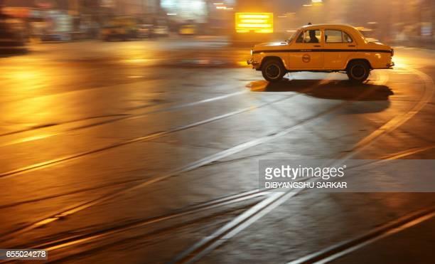 In this photograph taken on February 14 an Indian Hindustan Motors Ambassador taxi crossed tramlines on a street in Kolkata India's Hindustan Motors...