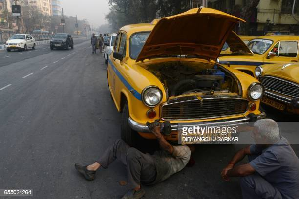 In this photograph taken on February 14 an Indian mechanic works on a Hindustan Motors Ambassador taxi parked on a roadside in Kolkata India's...