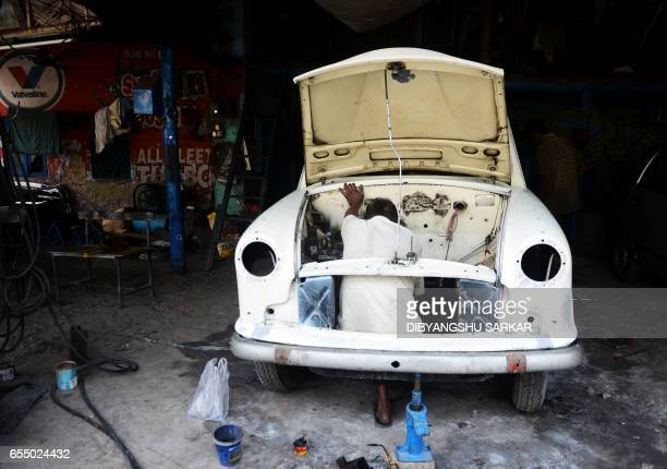 In this photograph taken on February 17 an Indian mechanic works on Hindustan Motors Ambassador cars at a small roadside workshop in Kolkata India's...