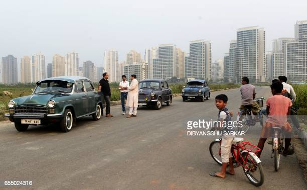 In this photograph taken on February 19 Indian children look on as owners of private Hindustan Motors Ambassador cars park in front of new apartment...