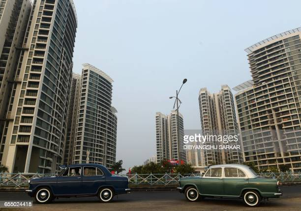 In this photograph taken on February 19 Indian owners of private Hindustan Motors Ambassador cars park in front of new apartment buildings in Kolkata...