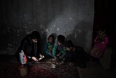 In this photograph taken on February 19 nine yearold Afghan Zilgai a water seller counts his money with his father Tariq Safi and his sister...
