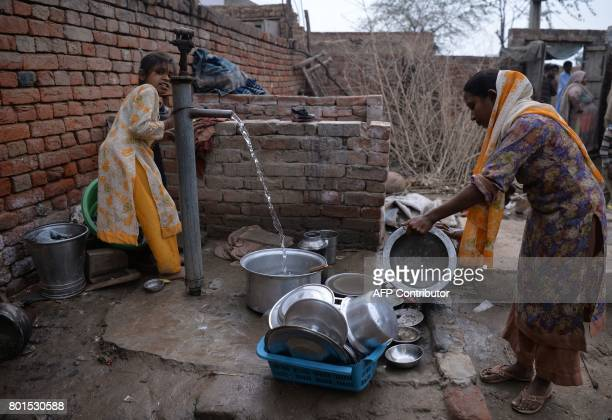 In this photograph taken on February 2 thirtyyearold Bushra Bibi who sold one of her kidneys cleans dishes with her daughter in a courtyard at her...
