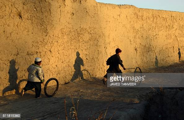 TOPSHOT In this photograph taken on February 22 2016 Afghan boys play with a tyre outside their house in the Zhari district of Kandahar province AFP...