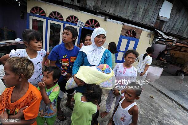 In this photograph taken on February 24 2011 Indonesian mother Erni wife of a fisherman carries her twoyear old baby boy Bili at a fishing village in...