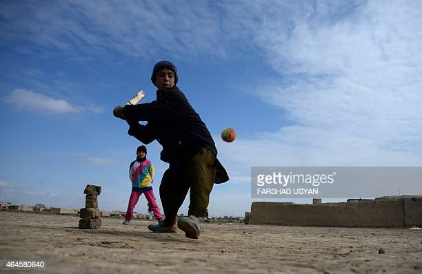 In this photograph taken on February 26 Afghan children play cricket with a makeshift wicket and bat in a refugee camp on the outskirts of...