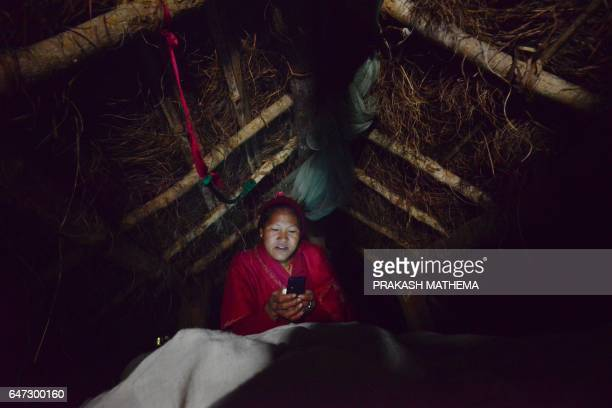 In this photograph taken on February 3 Nepalese woman Pabitra Giri looks at her mobile in a Chhaupadi hut during her menstruation period in Surkhet...