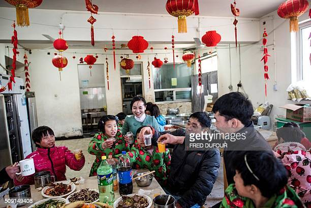 In this photograph taken on February 7 children and adults raise their cups in a toast as they eat their lunch in an orphanage on the outskirts of...