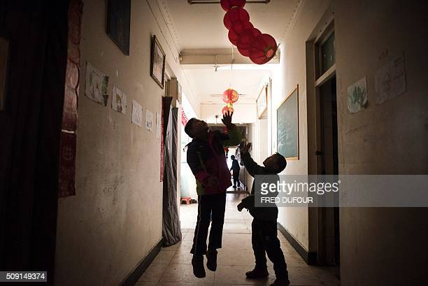 TOPSHOT In this photograph taken on February 7 children play with red lanterns in an orphanage on the outskirts of Beijing the eve of the Lunar New...