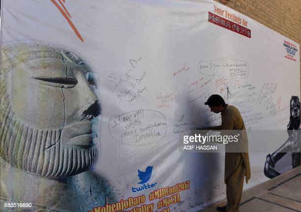 In this photograph taken on February 9 a Pakistani visitor writes on a banner during an international conference near the UNESCO World Heritage...