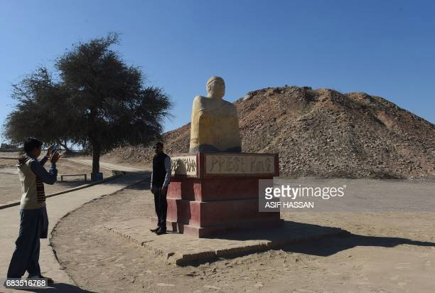In this photograph taken on February 9 a visitor takes a photograph beside of replica of a statue of King Priest discovered at the UNESCO World...