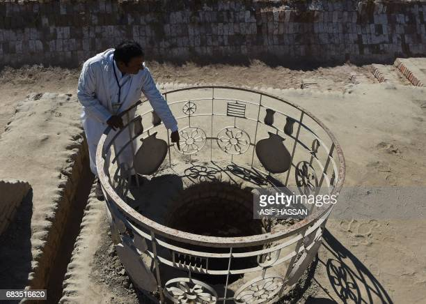 In this photograph taken on February 9 Pakistani caretaker at the UNESCO World Heritage archeological site of Mohenjo Daro Ismail Mugheri points out...