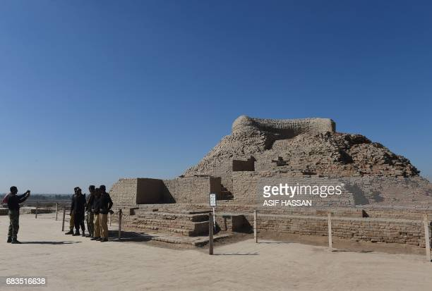 In this photograph taken on February 9 Pakistani policemen take a photograph alongside a Buddhist stupa at the UNESCO World Heritage archeological...