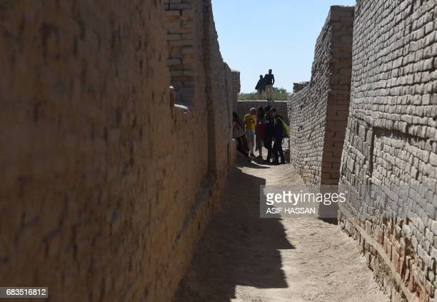 In this photograph taken on February 9 visitors walk through the UNESCO World Heritage archeological site of Mohenjo Daro some 425 kms north of the...