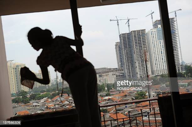 In this photograph taken on Januar 22 a house maid cleans an apartment window in Jakarta while a construction site for high rise commercial and...