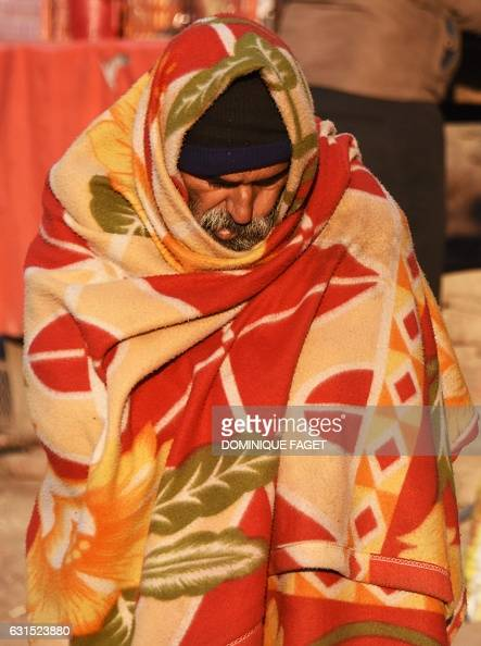 In this photograph taken on January 10 an Indian men wrapped in a blanket sits on the street on a cold morning in New Delhi A cold wave is sweeping...