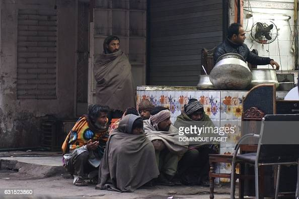In this photograph taken on January 10 homeless Indian men wrapped in blankets waiting for donors to purchase food for them from a stall on a cold...