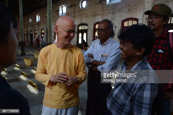 In this photograph taken on January 14 multiawarded German conceptual artist Wolfgang Laib speaks with a group of Myanmar artists in the hallway of...