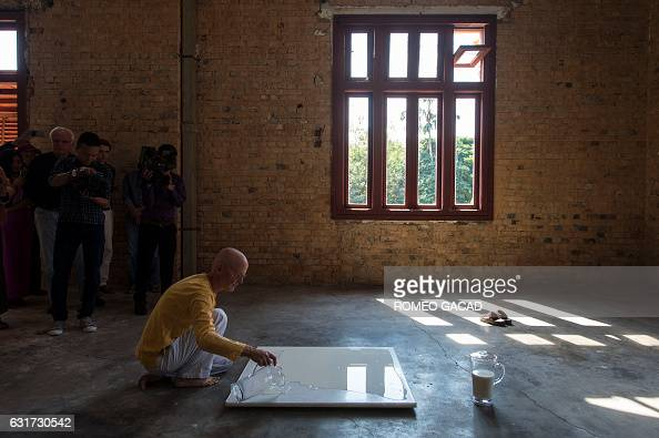 In this photograph taken on January 14 multiawarded German conceptual artist Wolfgang Laib pours milk on a polished marble part of his exhibition...