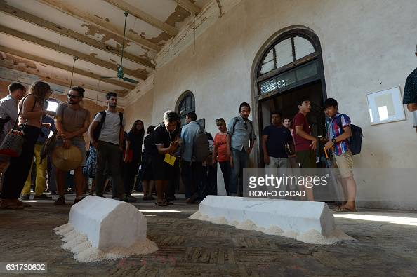 In this photograph taken on January 14 visitors look at an art installation made of unpolished marble surrounded by a layer of rice created by...