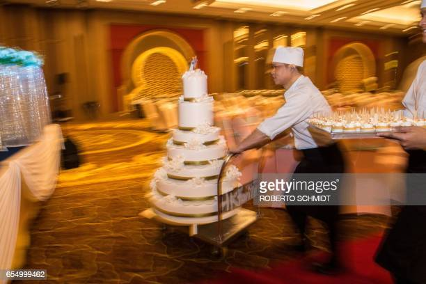 In this photograph taken on January 15 a pastry chef pushes a cart loaded with a wedding cake before a wedding reception at the Al Meroz hotel in...