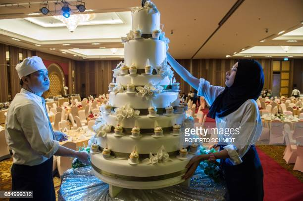 In this photograph taken on January 15 pastry chefs adorn a wedding cake before a wedding reception at the Al Meroz hotel in Bangkok From hotels with...