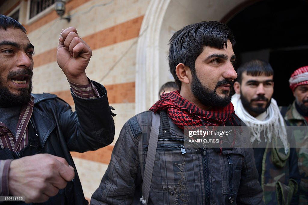In this photograph taken on January 17, 2013 former Syrian army soldiers Ali Naema (C), who defected and joined rebels, stands outside the compound in Aleppo. Just a few months ago, Ali Naema was playing a trumpet in the Syrian army. AFP PHOTO/AAMIR QURESHI