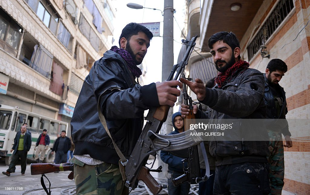 In this photograph taken on January 17, 2013 former Syrian army soldiers Ali Naema (R) and Amar (L), who defected and joined rebels, exchange AK-47 guns outside their compound in Aleppo. Just a few months ago, Ali Naema was playing a trumpet in the Syrian army. AFP PHOTO/AAMIR QURESHI