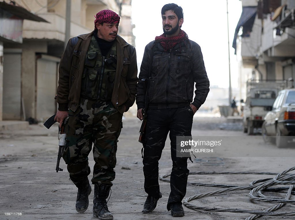 In this photograph taken on January 17, 2013 former Syrian army soldiers Ali Naema (R), who defected and joined rebels, chats with his comrade outside their compound in Aleppo. Just a few months ago, Ali Naema was playing a trumpet in the Syrian army. AFP PHOTO/AAMIR QURESHI