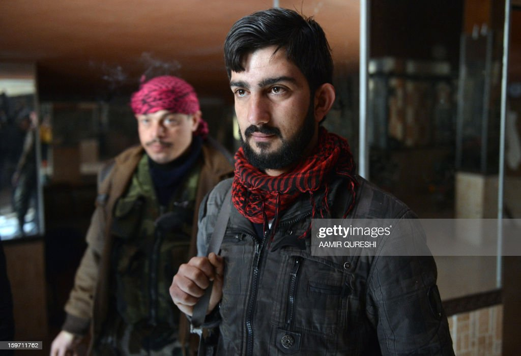 In this photograph taken on January 17, 2013 former Syrian army soldiers Ali Naema, who defected and joined rebels, stands inside the compound in Aleppo. Just a few months ago, Ali Naema was playing a trumpet in the Syrian army.