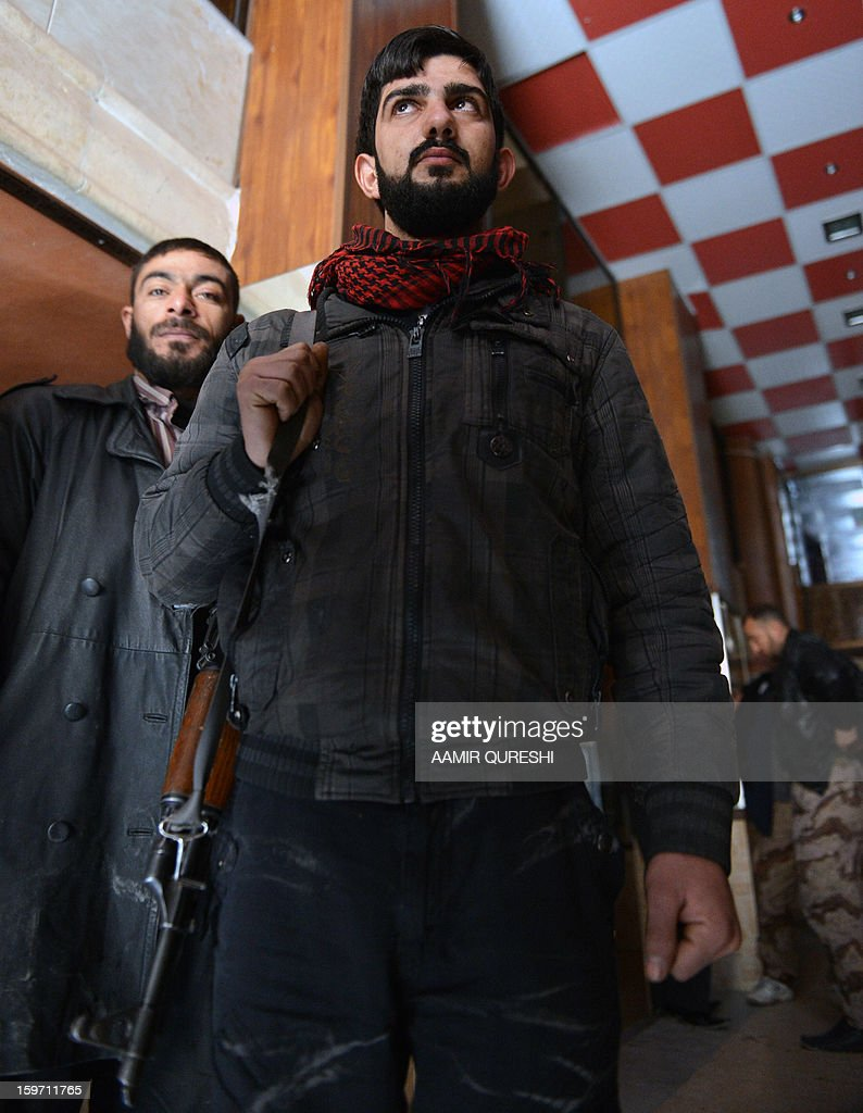 In this photograph taken on January 17, 2013 former Syrian army soldiers Ali Naema (R), who defected and joined rebels, stands inside the compound in Aleppo. Just a few months ago, Ali Naema was playing a trumpet in the Syrian army.