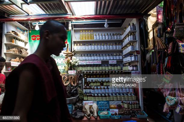 In this photograph taken on January 19 a Buddhist monk passes a traditional medicine shop selling elephant parts and other rare wildlife at the...