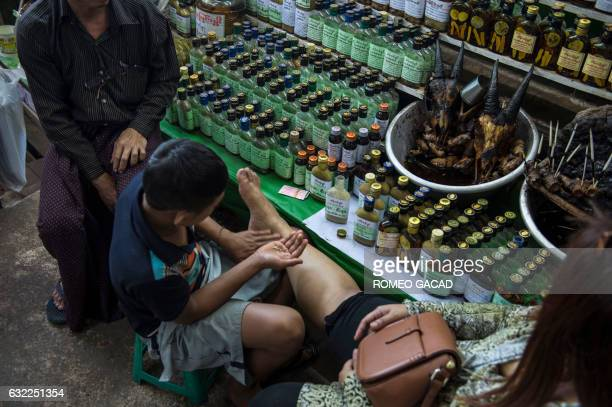In this photograph taken on January 19 a customer is massaged with lotion mixed with oil from rare animals and plants at a traditional medicine shop...