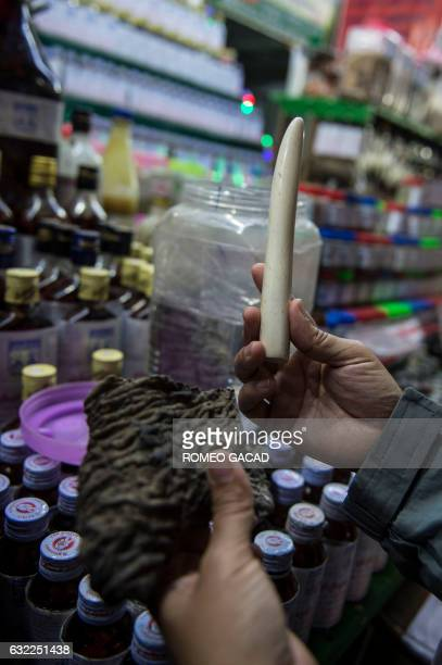 In this photograph taken on January 19 a customer looks at chunk of dried elephant skin seen at left and an ivory tusk seen at right for sale at the...