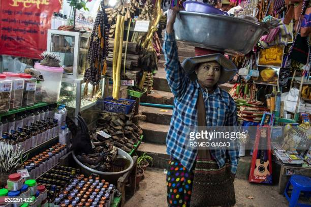 In this photograph taken on January 19 a vendor pass a traditional medicine shop seen at left selling elephant parts and other rare wildlife at the...
