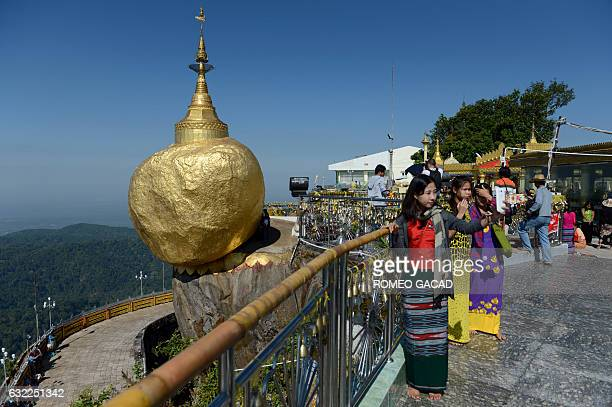 In this photograph taken on January 19 pilgrims take photos at the Golden Rock pagoda in Mount Kyaikhteeyoe surrounded by souvenir shops restaurants...