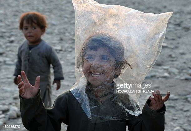 In this photograph taken on January 2 2015 Afghan internally displaced children play outside their shelter on the outskirts of Jalalabad in Nangarhar...
