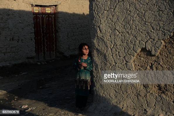 TOPSHOT In this photograph taken on January 21 an Afghan girl stands alongside a wall on the outskirts of Jalalabad / AFP / NOORULLAH SHIRZADA