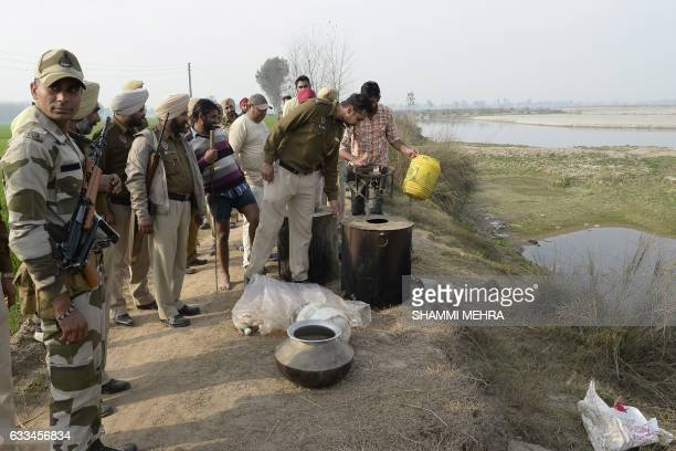 In this photograph taken on January 24 Indian police recover equipment used to make raw alcohol during a search at Dhole Wal village in Dharamkot...