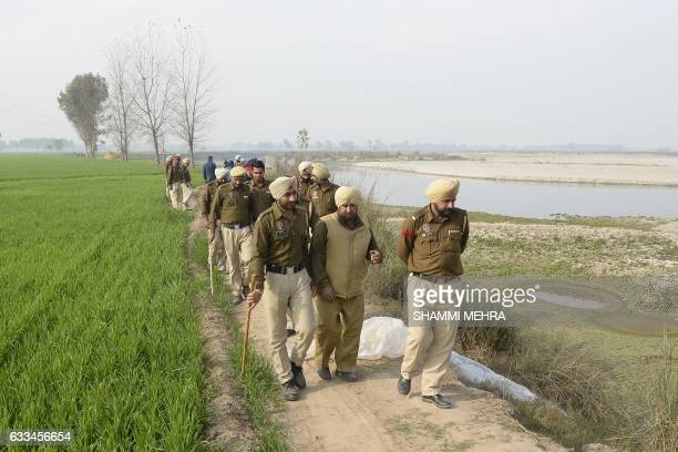 In this photograph taken on January 24 Indian police take part in a search to recover equipment used to make raw alcohol during a search at Dhole Wal...