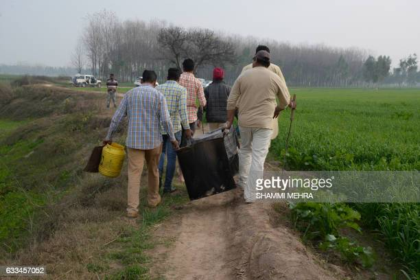 In this photograph taken on January 24 Indian villagers help police to remove equipment used to make raw alcohol during a search at Dhole Wal village...