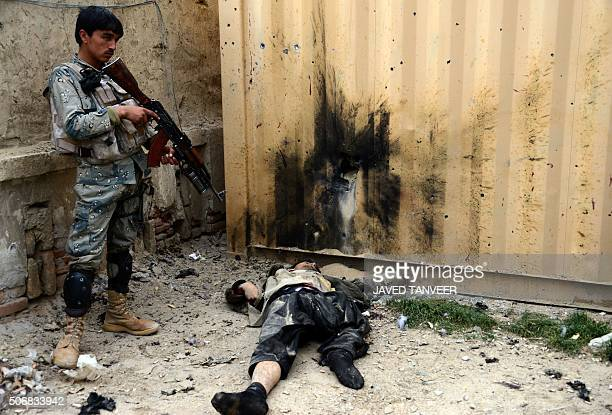 TOPSHOT In this photograph taken on January 25 an Afghan Border Police personnel stands over the body of a militant after Taliban attackers stormed a...