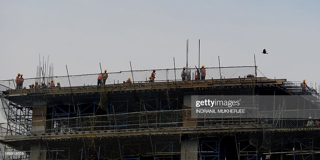 In this photograph taken on January 27, 2013, Indian labourers work on a building in Mumbai. India's central bank cut its main interest rates by 25 basis points on January 29, 2012, in its first reduction for nine months as it seeks to kick start the slowing economy. The Reserve Bank of India (RBI) said the benchmark repo rate, at which it lends to commercial banks, would fall to 7.75 percent. AFP PHOTO/ INDRANIL MUKHERJEE