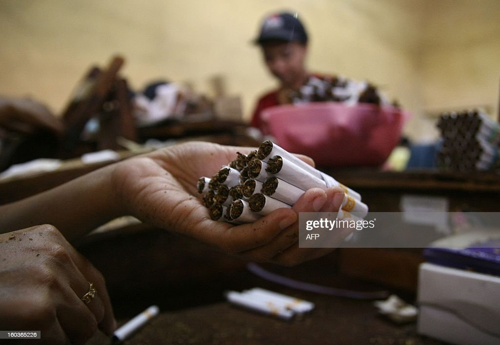 In this photograph taken on January 29, 2013 a person holds cigarettes in a local Indonesian tobacco company employing 600 women workers in Malang located in East Java province. Indonesian President Susilo Bambang Yudhono signed a tobacco regulation on December 24, 2012 in an effort to curb tobacco consumption which has faced staunch opposition from the cigarette lobby. More than 237,000 people work in the country's tobacco industry, producing some 190 billion cigarettes, according to data from the World Health Organization.