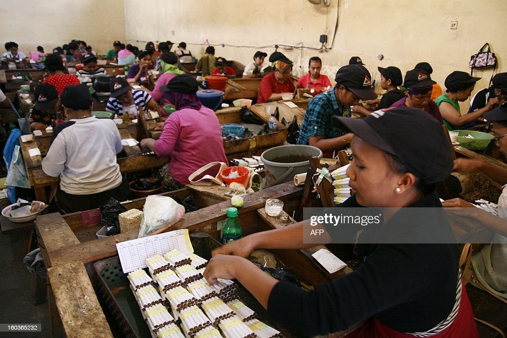 In this photograph taken on January 29, 2013 employess work in a local Indonesian tobacco company employing 600 women workers in Malang located in East Java province. Indonesian President Susilo Bambang Yudhono signed a tobacco regulation on December 24, 2012 in an effort to curb tobacco consumption which has faced staunch opposition from the cigarette lobby. More than 237,000 people work in the country's tobacco industry, producing some 190 billion cigarettes, according to data from the World Health Organization.
