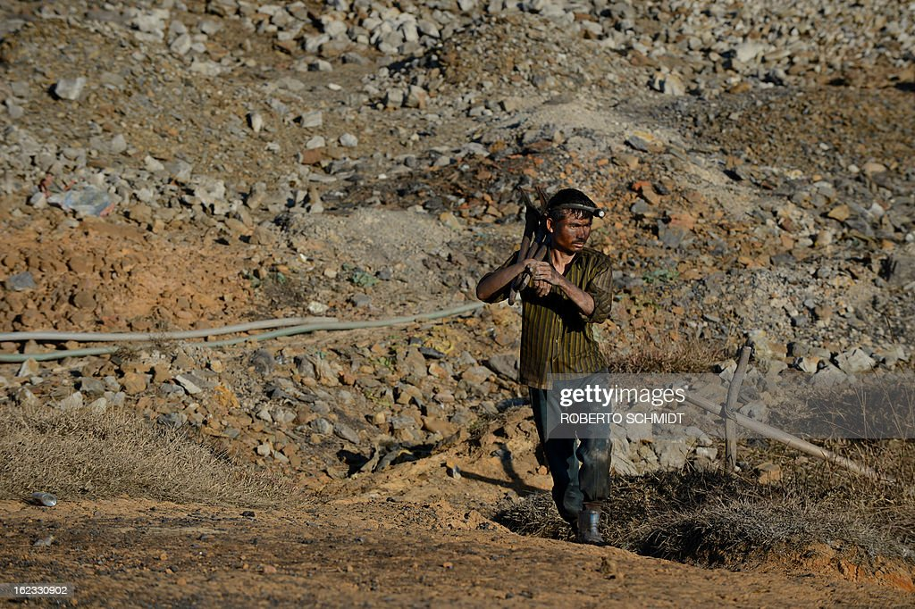 In this photograph taken on January 29, 2013, a miner carries his axe picks as emerges from a deep mine shaft after a long day scraping coal from small tunnels deep underground near Mulang village in the Indian northeastern state of Meghalaya. Thousands of private mines employ slim men and boys that will fit in thin holes branching out from deep shafts dug out from the ground in the East Jaintia Hills in Northeastern Indian state of Meghalaya. This state is the only state in India where coal mining is done privately by mine owners, who use cheap labour to supply the demand for this energy resource. Accidents and quiet burials are commonplace, with years of uncontrolled drilling making the rat-hole mines unstable and liable to collapse at any moment. After decades of unregulated mining, the state is due to enforce its first-ever mining policy later this year. AFP PHOTO/ Roberto Schmidt
